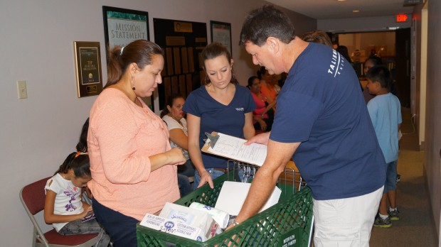 Sabrina Waggoner and Scott Tompkins, Talisman Energy employees are shown loading school supplies for a parent during the 2014 Interfaith of The Woodlands Kits4Kidz school supply program.  Talisman Energy is a sponsor of the annual Kits4Kidz school supply distribution program.