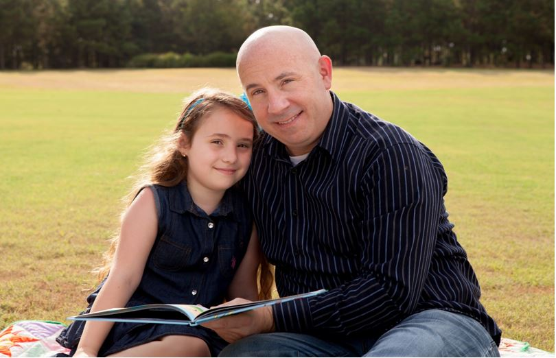 John Anthony Brown, newest member of The Woodlands Preparatory School Advisory Board, studies with his daughter, Madison, 8, in Creekside Park, The Woodlands.